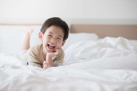 白いベッドの上に横になっているかわいいアジアの子