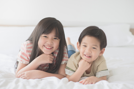 sister: Cute asian children lying on white bed