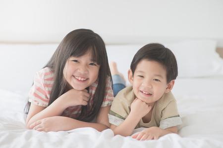 Niños asiáticos lindos que mienten en la cama blanca