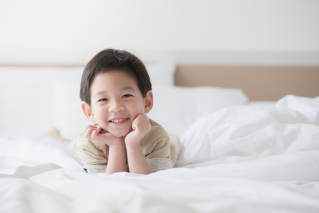 Cute asian child lying on white bed