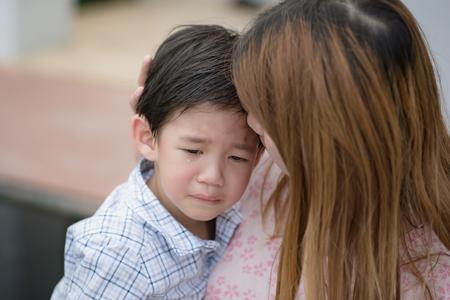 Aziatische moeder omarmen en troosten haar zoon