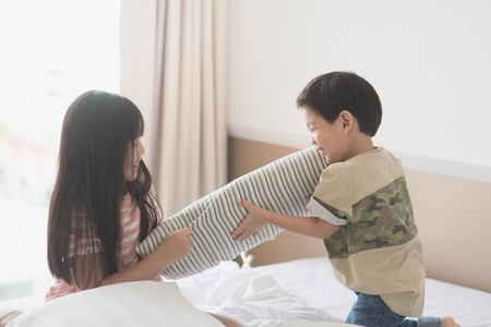 brother sister fight: Happy Asian child having Pillow Fight in Hotel Room Stock Photo
