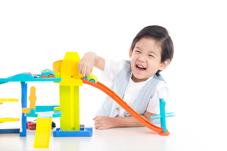 Cute Asian child playing toy cars on white background isolated