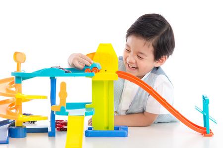 enfant qui joue: enfant jouant voitures jouets asiatiques mignon sur fond blanc isolé