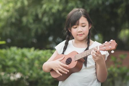 美しいアジアの少女屋外ポートレート、ウクレレを演奏