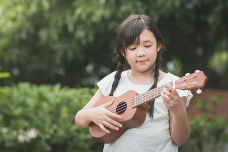 Beautiful asian girl playing ukulele, Outdoor portrait Reklamní fotografie