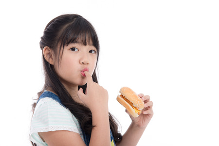 Beautiful asian girl eating hamburger on white background isolated