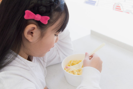 health food store: Asian girl eating Spaghetti Carbonara in convenience store Stock Photo