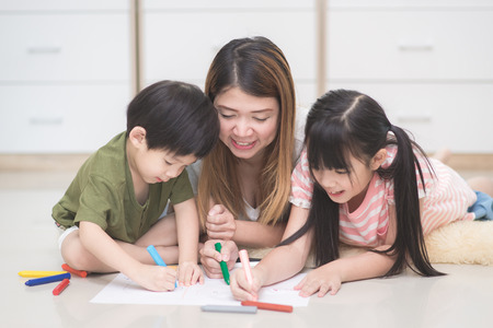 Asian family drawing picture with crayons