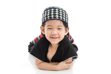 Cute muslim chlid lying on white background isolated.