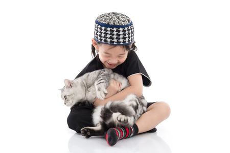 Cute muslim child playing with tabby cat on white background isolated.