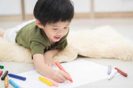 Cute Asian child drawing picture with crayon Imagens - 61504264