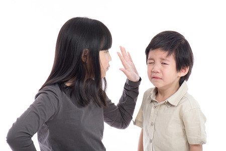 sibling rivalry: Asian sister and brother quarreling on white background isoated