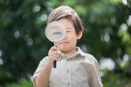 educacion ambiental: Asian boy with magnifying glass outdoors