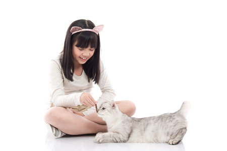 Beautiful Asian girl feeding snack to cute kitten on white background isolated Stock Photo
