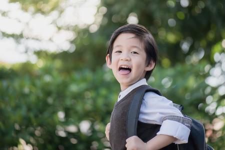niño con mochila: Retrato del estudiante asiático con el morral al aire libre, de vuelta al concepto de escuela