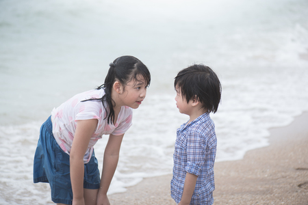 Beautiful Asian girl is comforting her crying brother on the beach Stock Photo