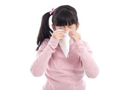 Belle fille asiatique souffle son nez sur fond blanc isolé