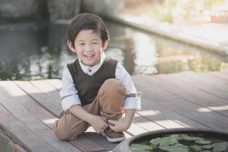 little asian child tying his shoes outdoors,vintage filter Stock Photo