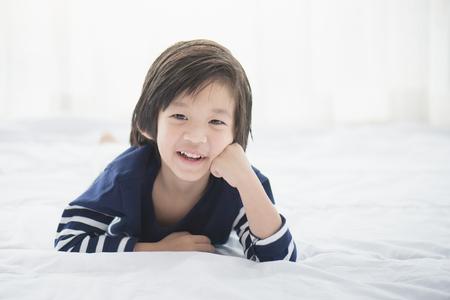 Leuk Aziatisch kind dat op wit bed ligt