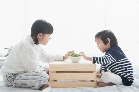 pigeon pea: Asian children eating green soybeans on white bed