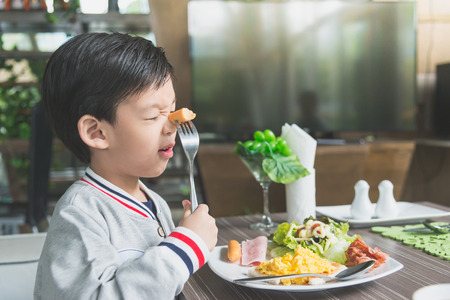 korean salad: Cute Asian child eating breakfast in a restaurant