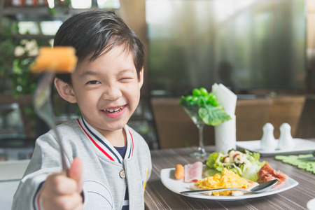 Cute Asian child eating breakfast in a restaurant