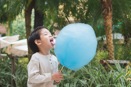 Cute Asian child eating blue cotton candy in the park