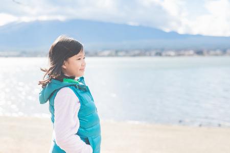 Portrait of happy beautiful Asian girl i at Kawaguchiko lake in Japan