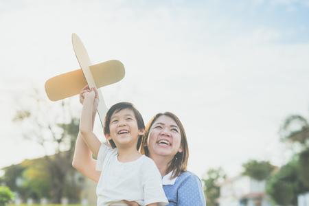 Leuke Aziatische moeder en zoon spelen kartonnen vliegtuig samen in het park buiten Stockfoto