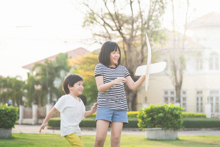 thee: Cute Asian children playing cardboard airplane together in thee park outdoors Stock Photo