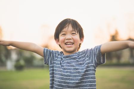 Het leuke Aziatische kind spelen piloot vlieger in u park buiten Stockfoto