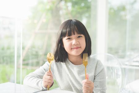 Schönes asiatisches Mädchen, das einen Löffel und eine Gabel mit leerer weißer Platte im Restaurant hält Standard-Bild - 72247498