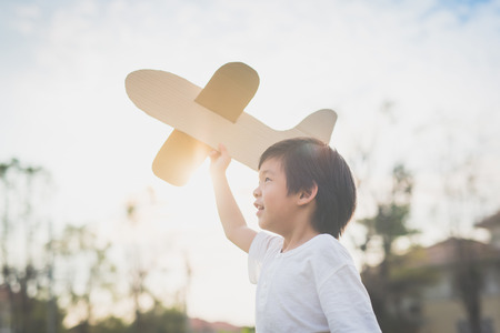 Cute Asian child playing cardboard airplane in thee park outdoors Stock Photo