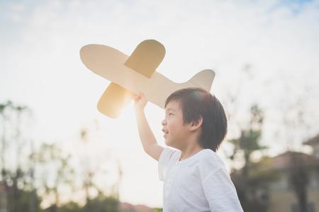 Nettes asiatisches Kind, das draußen Pappflugzeug in dir Park spielt