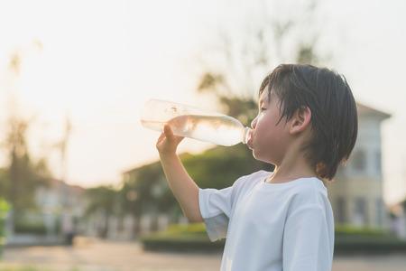 かわいいアジアの男の子は、屋外のボトルから水を飲む