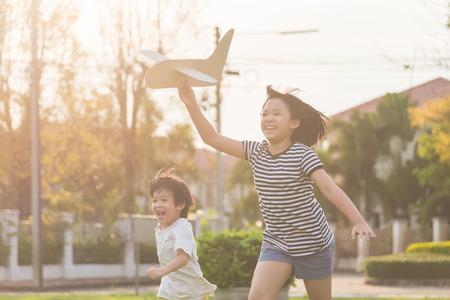 Het leuke Aziatische kinderen spelen kartonnen vliegtuig samen in u park buiten Stockfoto