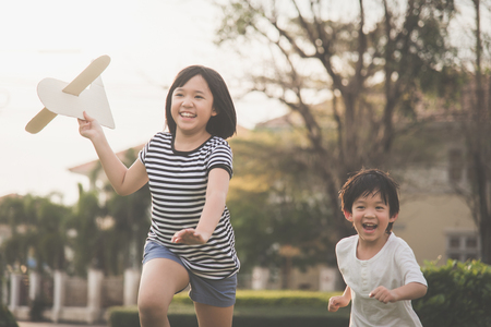 귀여운 아시아 어린이 함께 thee 공원 야외에서 골 판지 비행기를 연주