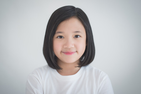 Sluit omhoog van het mooie Aziatische meisje glimlachen op grijze achtergrond