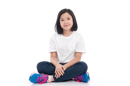 分離した白い背景の上に座ってアジア短い髪の少女 写真素材