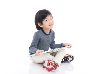 Cute asian boy reading a book on white background isolated
