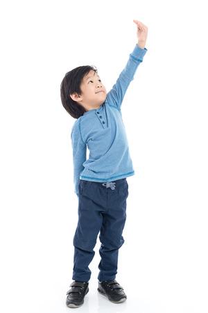 アジアの少年の背の高い成長と分離した白い背景に自分自身を測定 写真素材