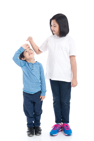 Asiangirl measures the growth of her brother on white background isolated