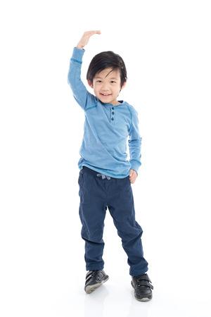 아시아 소년 높이 성장하고 격리 된 흰색 배경에 자신을 측정
