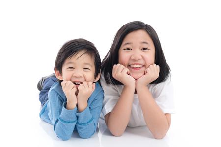 흰색 배경에 누워 귀여운 아시아 어린이는 격리