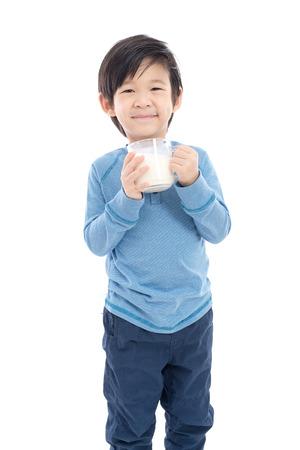 アジアの女の子は分離した白い背景のガラスから牛乳を飲む