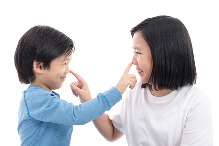 Cute asian children pointing at nose on white background isolated