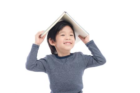 머리에 책을 흰색 배경에 고립에게에 생각 귀여운 아시아 소년