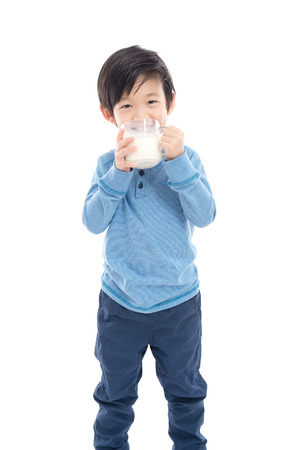 절연 흰색 배경에 유리에서 우유를 마시는 아시아 소녀