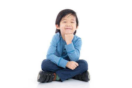 Gelukkige Aziatische jongenszitting op witte geïsoleerde achtergrond Stockfoto